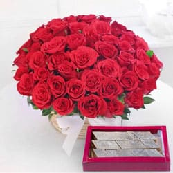 Astounding Red Roses with yummy Kaju Barfi to Bhalaswa